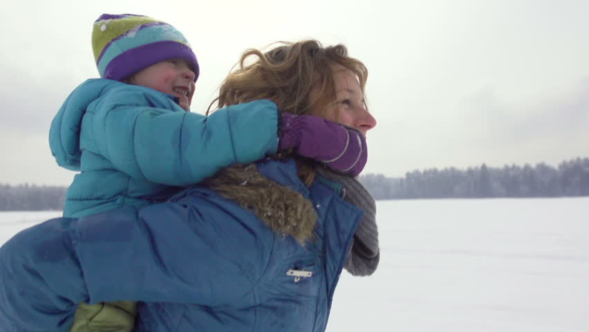 Beautiful Slow Motion Of Mother Carrying Her Three-Year-Old Son Piggyback And Running Over Snow Covered Field