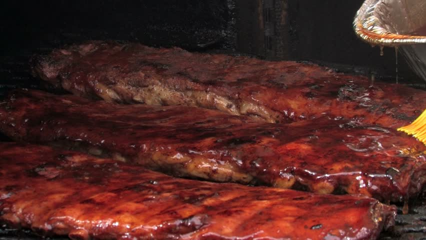 Basting barbecue ribs with juicy sauce on a grill