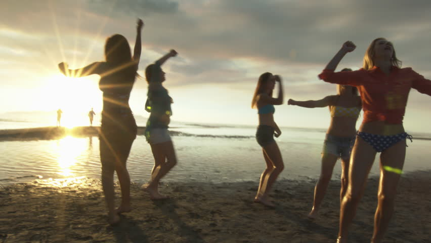 Group of Five Teenage Girls Dancing On The Beach At Sunset