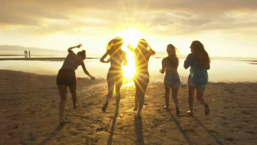 Group of Five Teenage Girls Run Into The Water, Celebrate On The Beach At Sunset