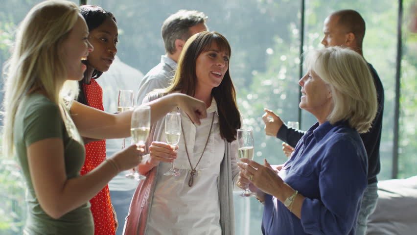 Diverse group of female friends chatting together and drinking wine at a party in contemporary home with natural view.