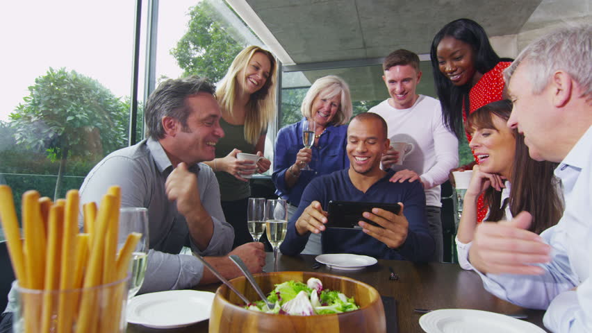 Cheerful diverse adult group, seated at table for dinner all crowd round to take a look at the screen of a computer tablet.