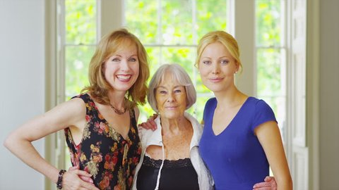 Portrait of three generations of beautiful women from the same family together at home. In slow motion.