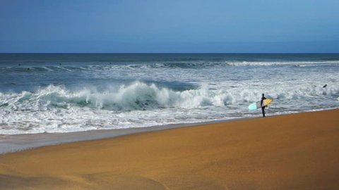 two longboard surfers paddle out at bells beach, victoria