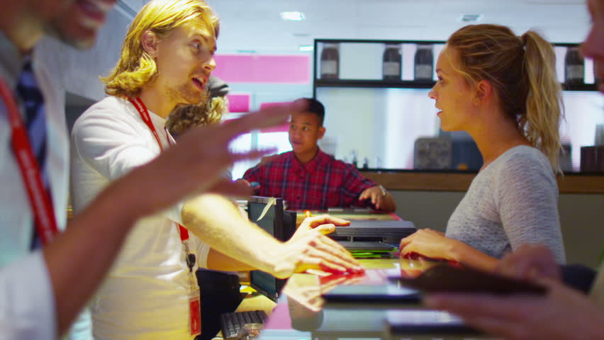 Team of staff dealing with customers at the reception area of informal business organization | Shutterstock HD Video #5261036