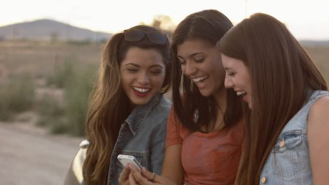 Multi Ethnic Group Of Teen Girls Laughing At A Phone Together In The Desert