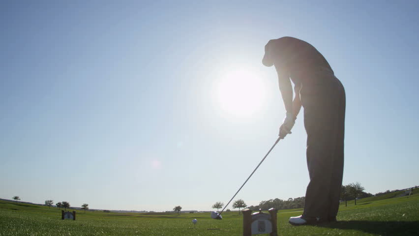 Professional male golfer working luxury vacation resort using driver preparing to tee off golf course fairway sun lens flare shot on RED EPIC, 4K, UHD, Ultra HD resolution | Shutterstock HD Video #5328776
