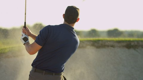 Caucasian male golfer playing weekend round golf concentrating on hitting his ball out of sand bunker shot on RED EPIC, 4K, UHD, Ultra HD resolution