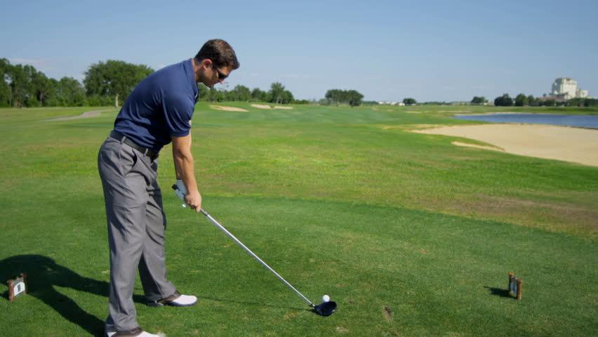 Professional Golfer Taking Swing Hitting Golf Ball Off Tee