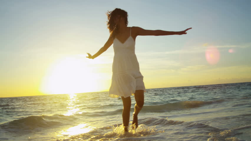 Pretty girl in sundress reveling being alone by ocean at sunrise on beach vacation shot on RED EPIC, 4K, UHD, Ultra HD resolution