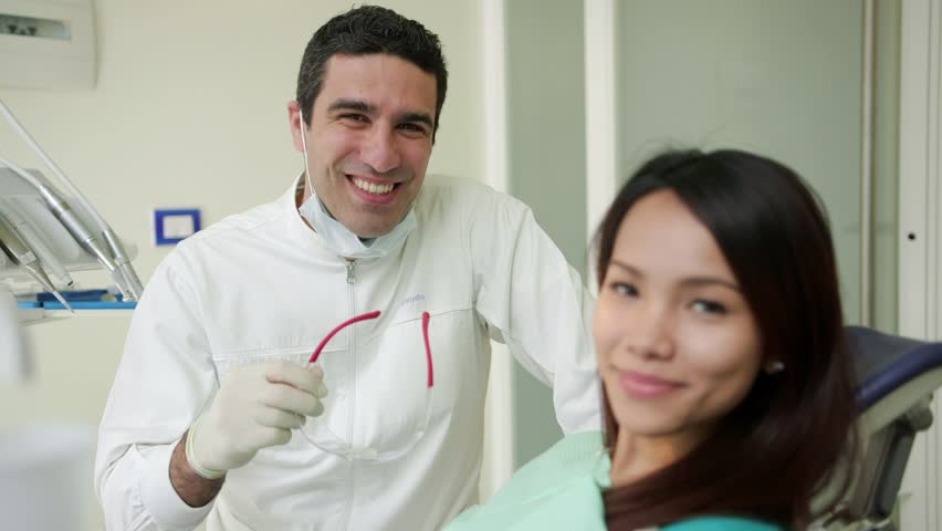 Portrait of happy hispanic man working as dentist in dental studio and young asian woman smiling, people and oral hygiene, health care in hospital. 7of19