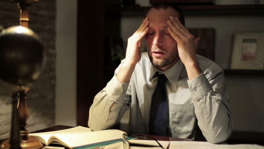 Overwhelmed businessman with headache working late at his office