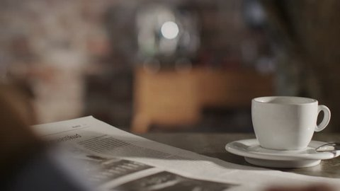 Man Reading Newspaper and Drink Coffee at Home.Shot on RED Digital Cinema Camera in 4K(ultra-high definition (UHD)),so you can easily crop, rotate and zoom, without losing quality!