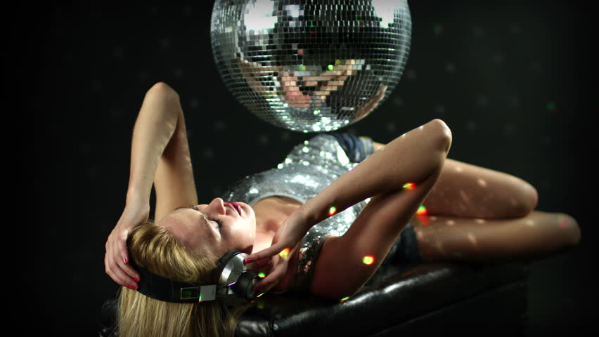 a sexy gogo dancer shot in a studio dancing and posing with a spinning disco ball. . this is a super high quality 4k version at 4096x2304 pixels