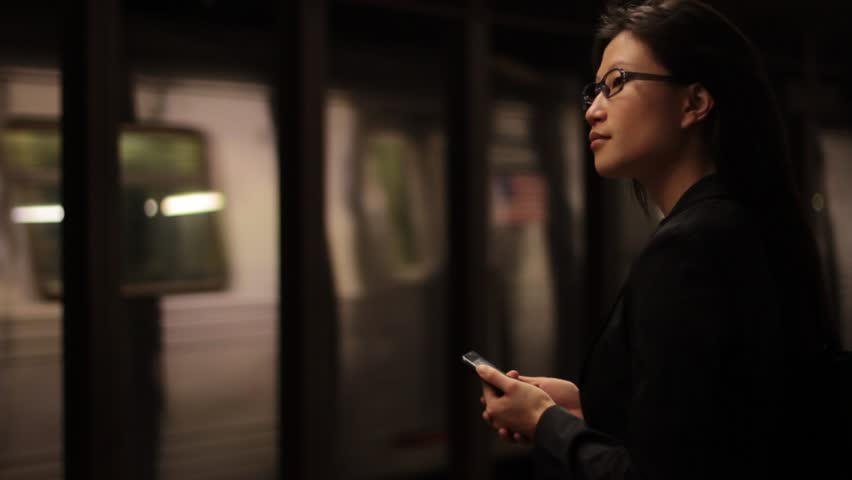 As a train passes, a woman checks her mobile device on the dark subway platform.