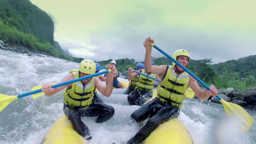 Team of six adult people white water rafting. On board camera, slow motion