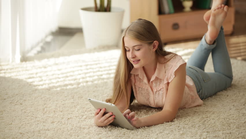 Young Woman Lying On The Floor Using A Tablet Computer Stock Footage Video 2220985 -6056