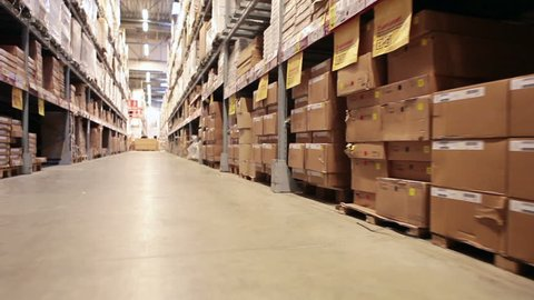 Moving camera along warehouse shelves with goods and materials