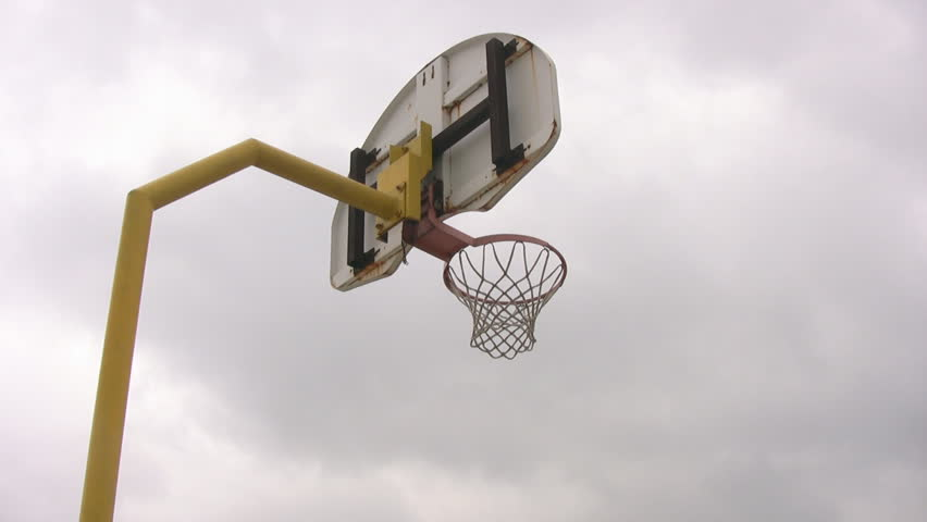 Looking up at an isolated outdoor basketball net, with an overcast, moody sky, moving in the background.
