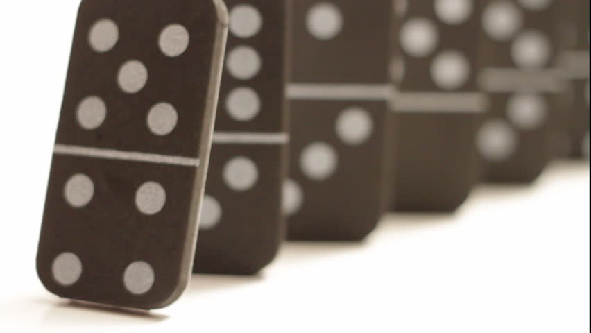 A bunch of dominoes falling in sequence, rack focus from the front domino to the back domino, isolated on white.