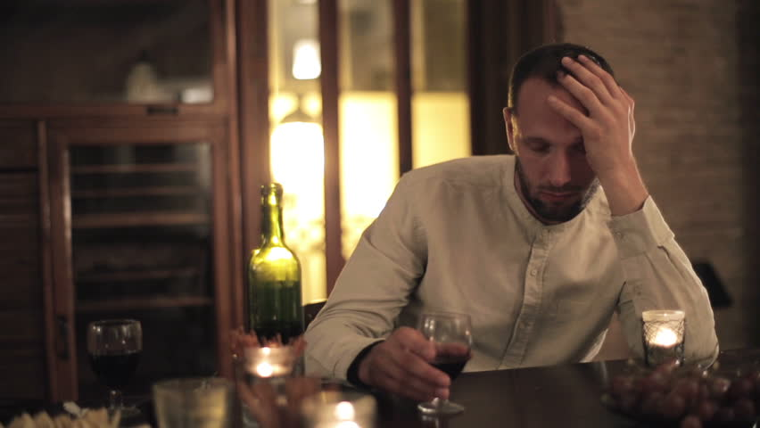 Lonely man drinking wine by the table at home, night time  | Shutterstock HD Video #5522216