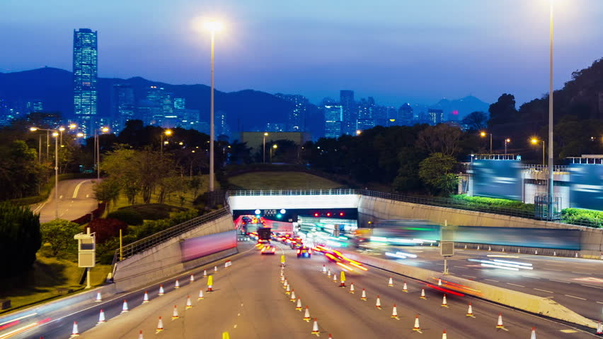 Sunset Busy Traffic Going Into Tunnel. Tight Zoom In Shot. Hong Kong rush hour sunset timelapse. Commercial Office Buildings with commercial billboards. Busy cars entering the cross harbor tunnel.   Shutterstock HD Video #5538536