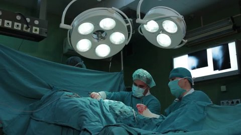 Surgeons team performing operation in hospital theater.Surgeons operating patient,hip replacement,low angle view,working with surgical instruments,using,scalpel,tweezers and pliers,cutting body.