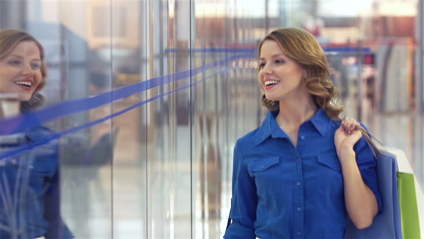 Joyful girl with purchases passing shopping windows