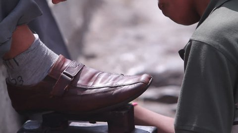 Child labor. Child works hard. Close-up of a child's hand cleaning shoes.Third world country