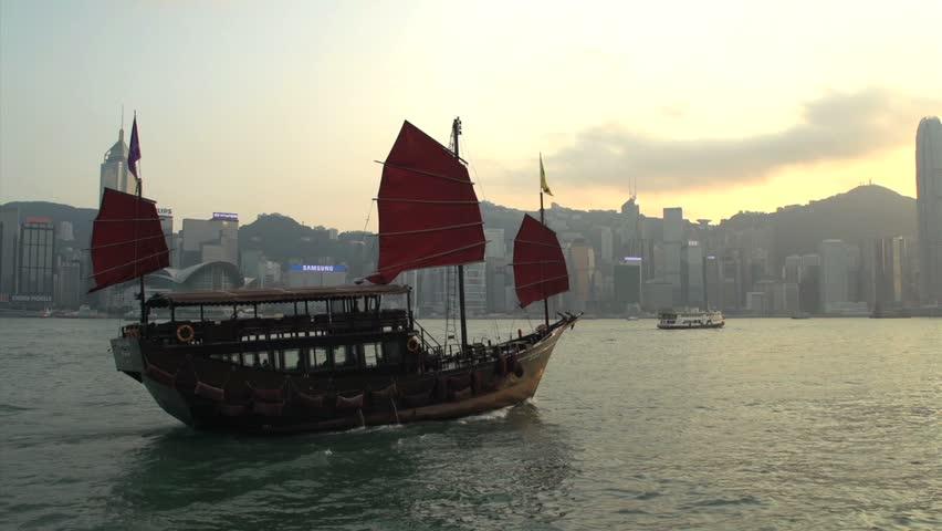 Junk ship in front of Hong Kong skyline during sunset | Shutterstock HD Video #5611580