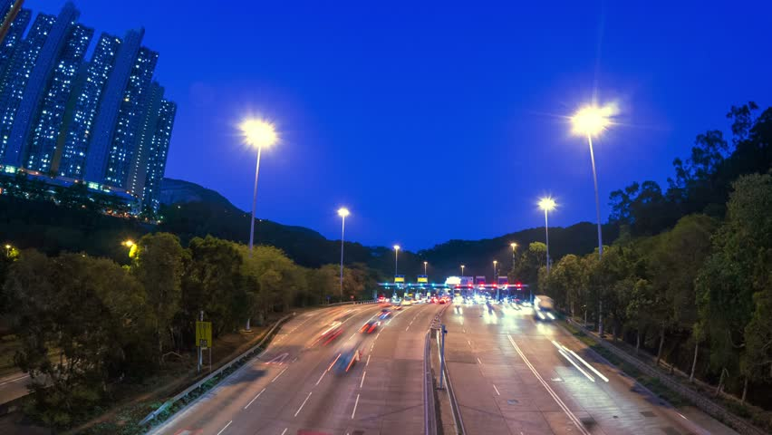 Highway Toll Booth. 4K Zoom In Shot. City Rush Hour. Cars line up on multiple lanes highway to the toll booths. Residential Buildings at the left.     Shutterstock HD Video #5615309