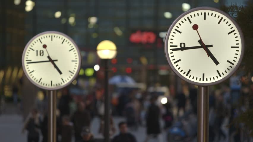 Commuters and Bankers head home past the Six Public Clocks on Reuters Plaza, Canary Wharf - a London Bus passes in the background