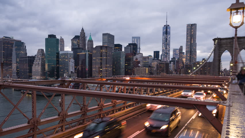 NEW YORK - JANUARY 15, 2014: Brooklyn Bridge timelapse with cars, beautiful Manhattan Skyline including Freedom Tower in New York. The Brooklyn Bridge is a suspension bridge in New York City.