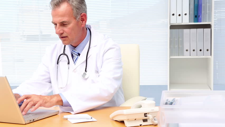 Doctor talking on phone and using laptop at his desk in his office at the hospital