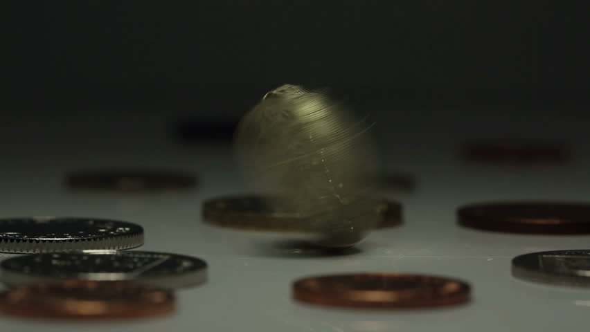 British One Pound coin spinning amongst other UK currency coins