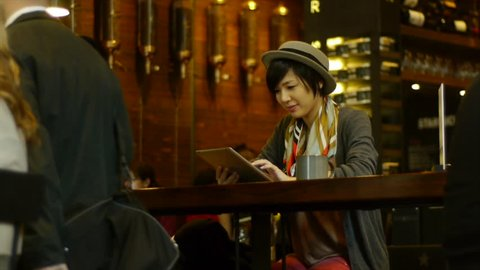Young Asian Woman With A Digital Tablet At A Busy Coffee Shop / Restaurant