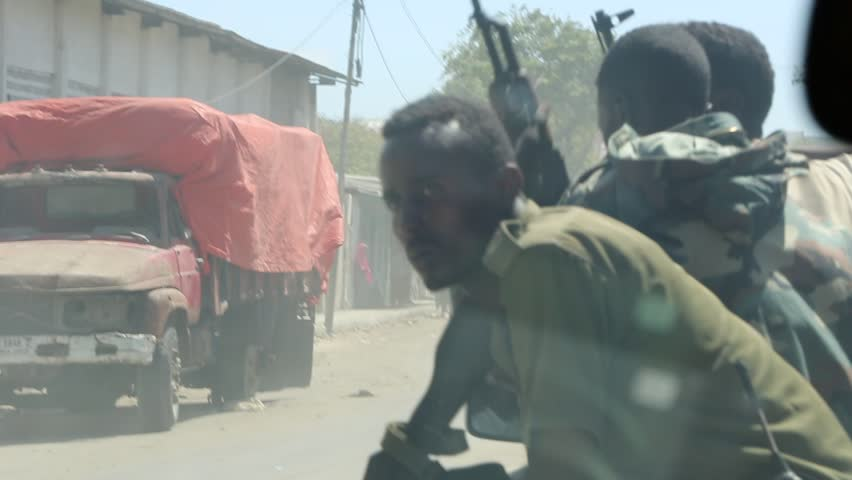 Mogadishu, Somalia, Circa 2013: A pickup truck of armed Somali soldiers waits for a military MRAP (Mine Resistant Ambush Protected) vehicle to pass on the streets of in Mogadishu, Somalia, Circa 2013.