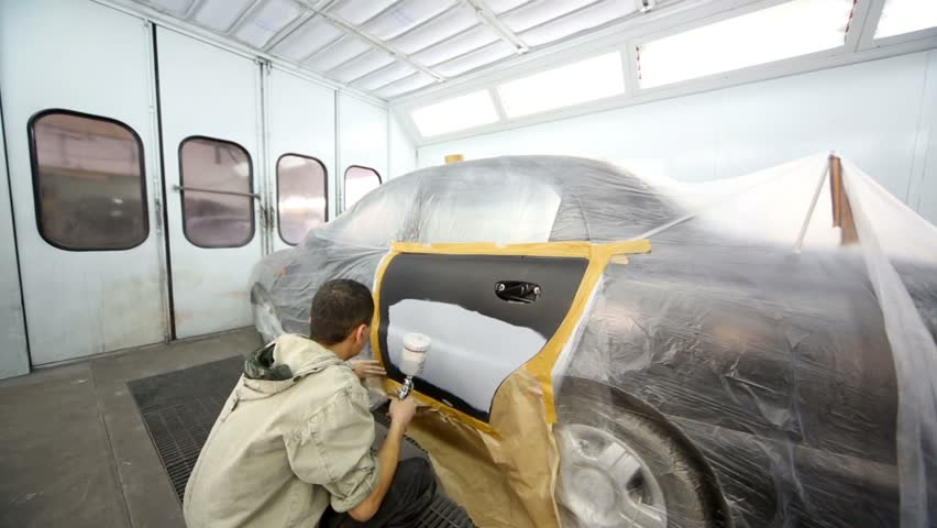 Man paints car door with automotive primer at painting booth