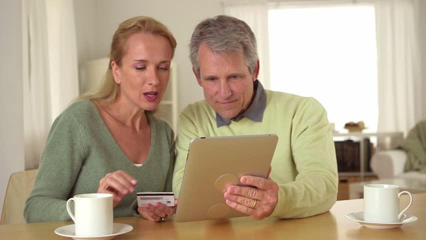 Senior couple using tablet at desk