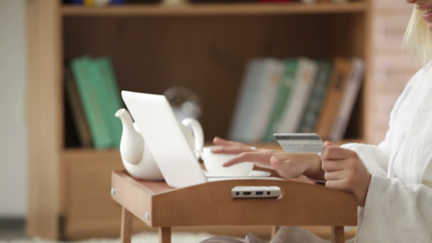 Attractive girl wearing bathrobe sitting on floor using laptop holding credit card looking at camera and smiling. Panning camera | Shutterstock HD Video #5690096