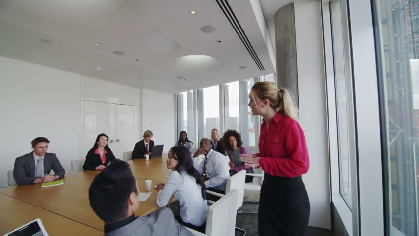 Corporate business team in boardroom meeting in city office.