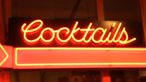Cocktails.   Neon Cocktails sign outside bar. Handheld with rack focus.