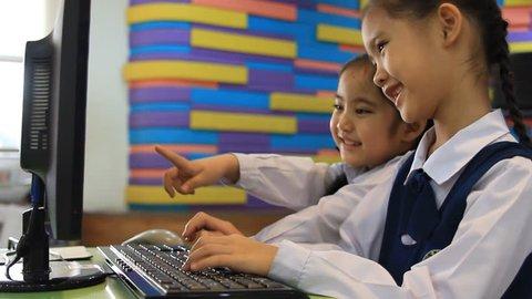 Little Asian children typing computer keyboard in computer class