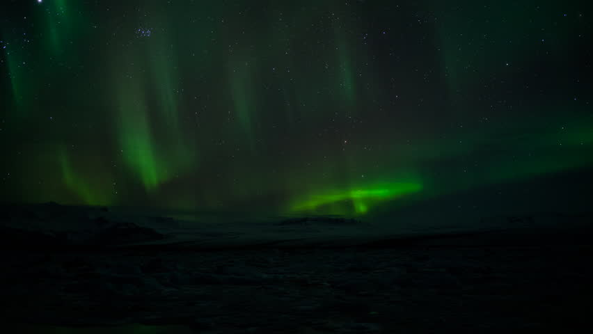Wide shot of Aurora Borealis over glacier mountains and lagoon in Iceland