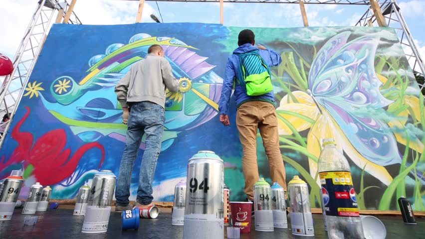 MOSCOW, RUSSIA - AUGUST 18, 2012: Two young men paint by sprays abstract graffiti during the festival Bright people