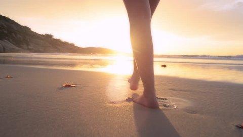 woman walking on beach barefoot sunset steadicam shot