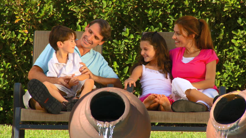 Attractive young caucasian family enjoying  leisure time together outdoors in their garden