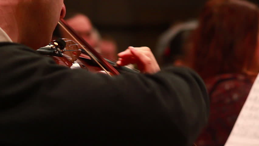 Male performs lead violin sole part playing at classical concert. Professional symphonic orchestra musicians at rehearsal, accompanying opera singer at theatre. Audience enjoying music, inner harmony