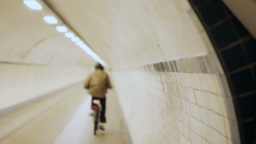 Shallow depth of field slow motion shot of an anonymous cyclist wearing a hoody, cycling his bicycle further into a white and grey concrete circular pipe shaped tunnel with a line of lights.