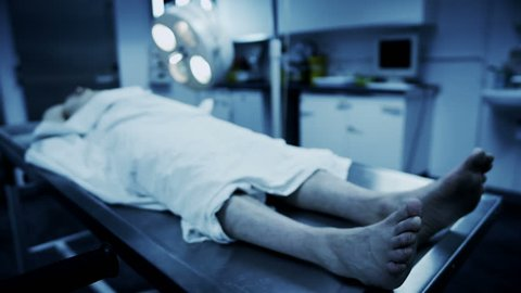 Dead male body laid out on an autopsy table